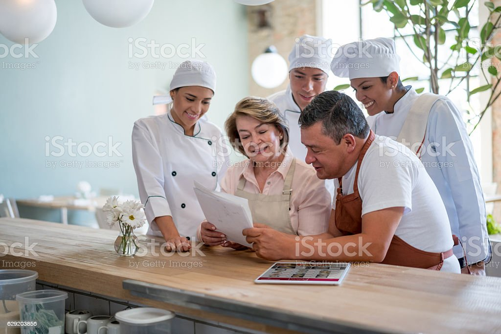 Business owner working at a restaurant with a group stock photo