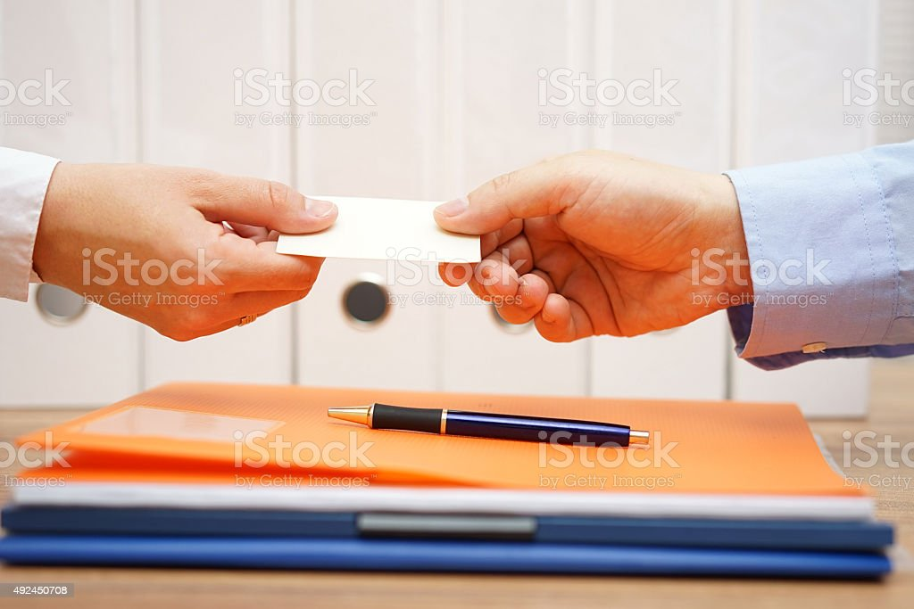 business partners are exchanging business cards over documents after meeting stock photo