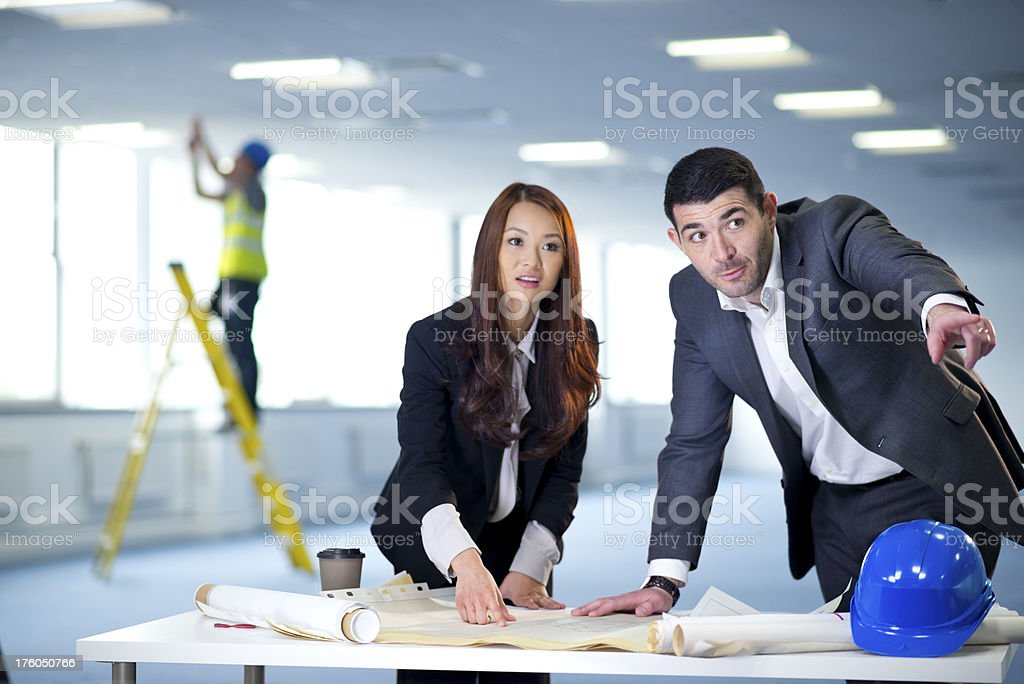 business partners discuss the new layout for their office interi royalty-free stock photo