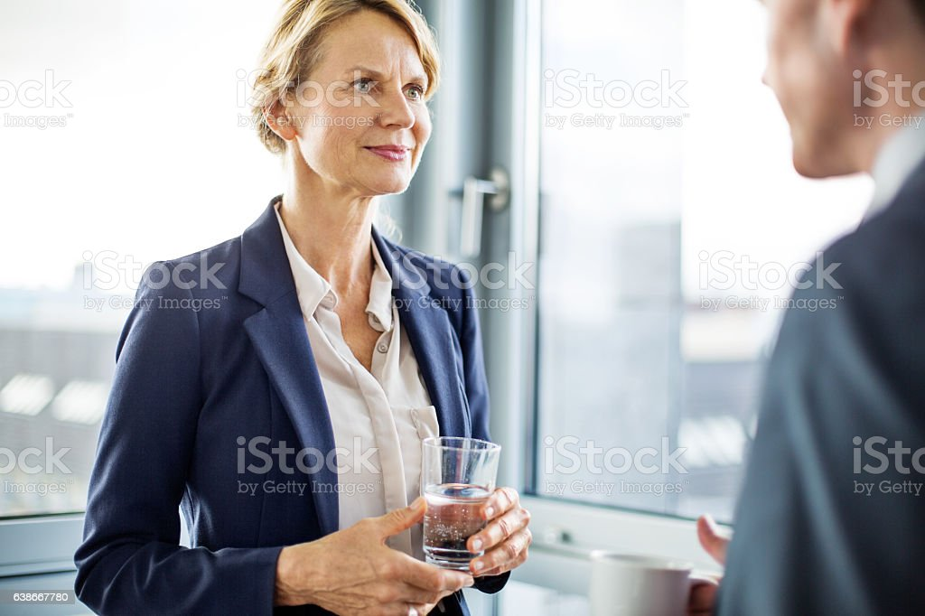 Business partners discussing during coffee break stock photo