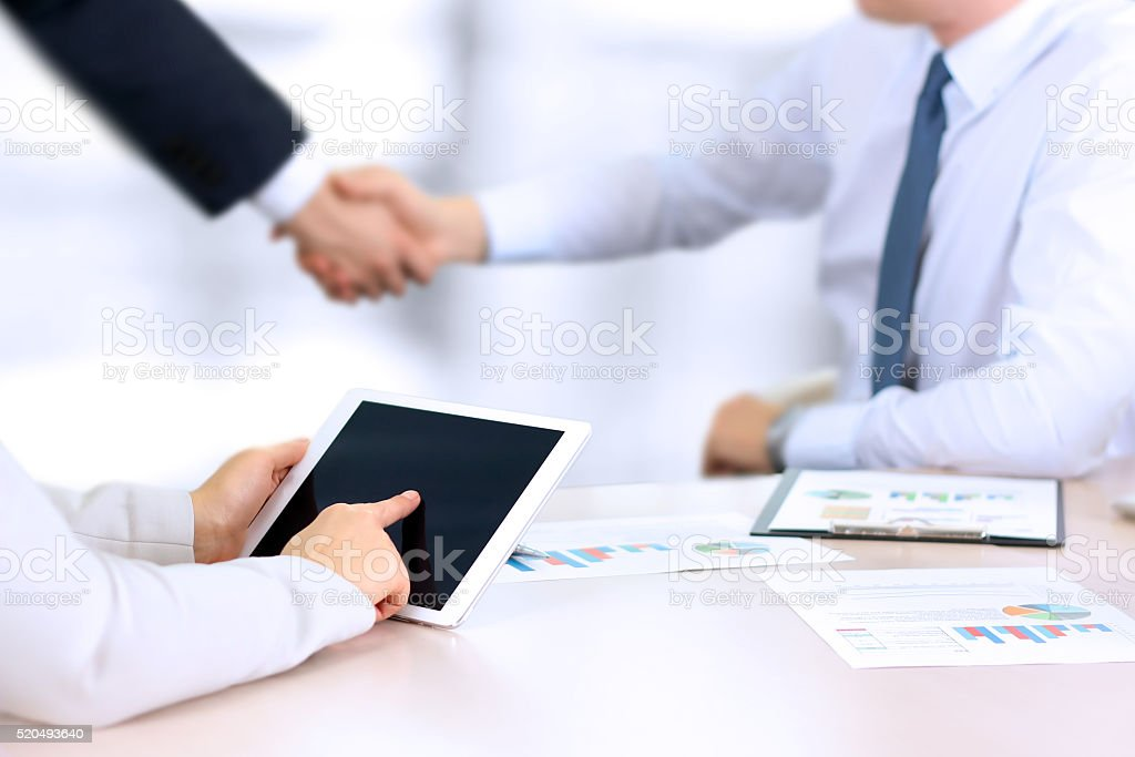 Business partners handshaking over business objects on workplace stock photo