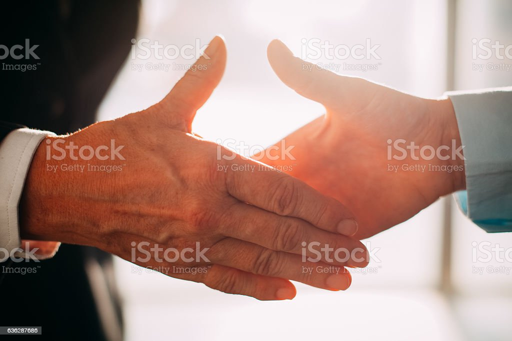 Business partners reaching hands to shake it stock photo