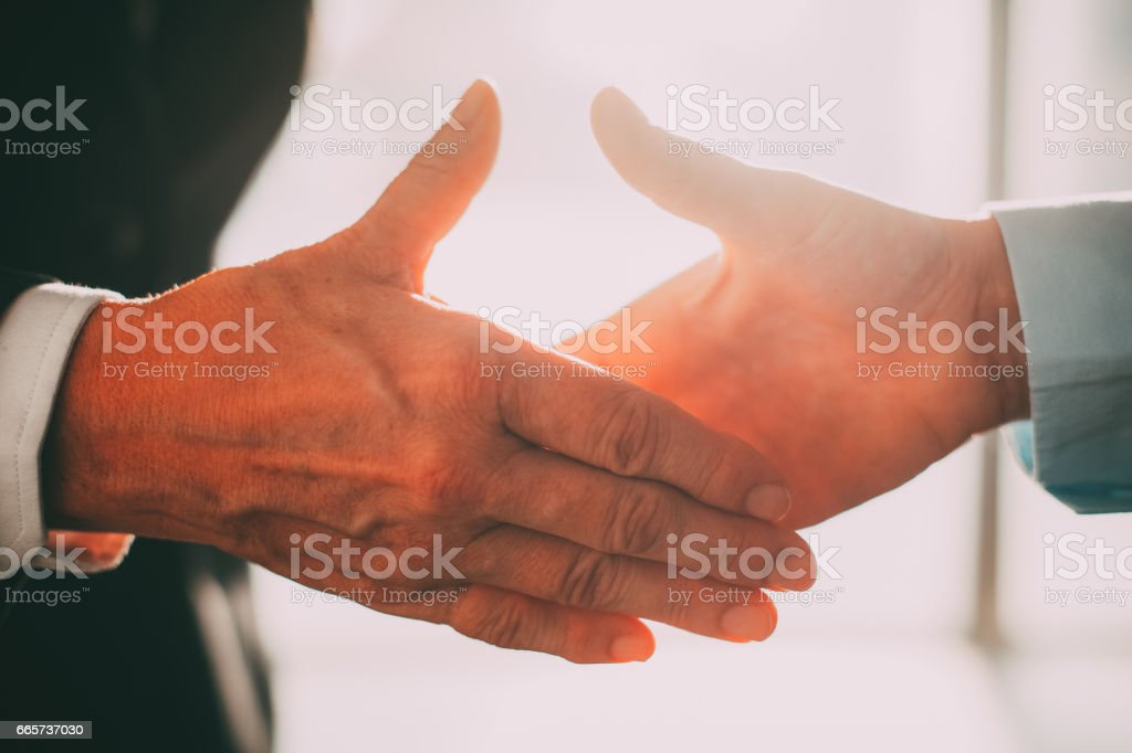 Business partners reaching hands to shake it_tone stock photo