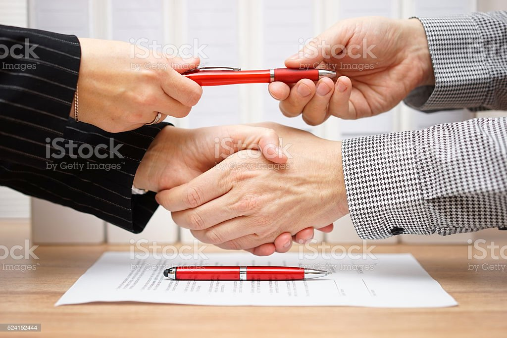 Business partners shaking hands and exchanging pen after finished deal stock photo