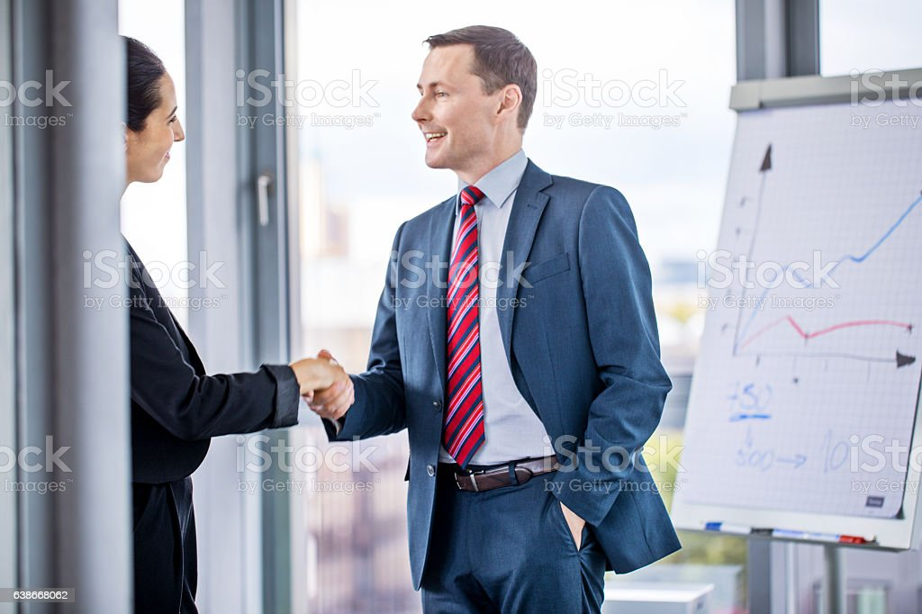 Business partners shaking hands in boardroom stock photo