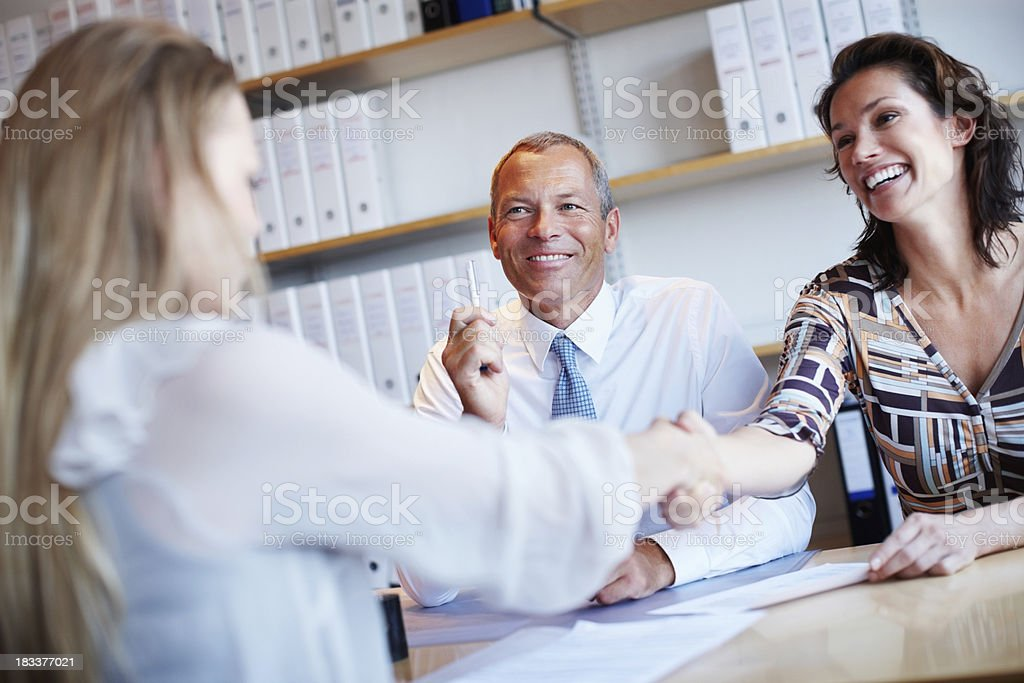 Business partners sitting at the table and shaking hands royalty-free stock photo