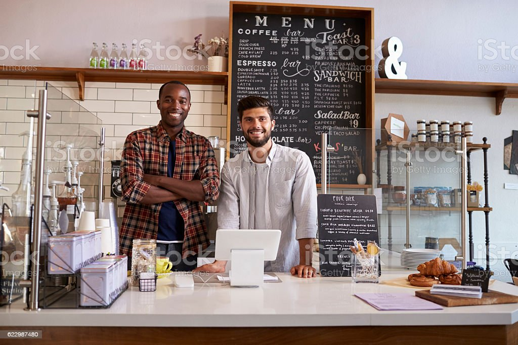 Business partners stand behind the counter at a coffee shop stock photo