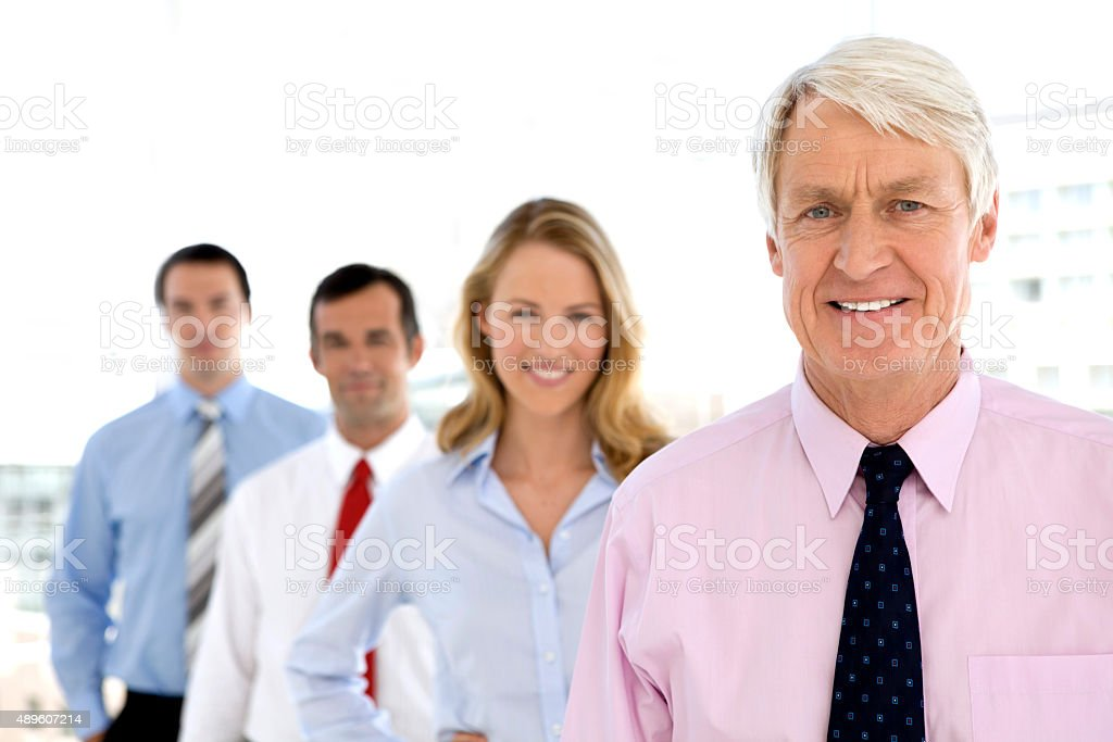 Business partners standing in row behind CEO stock photo