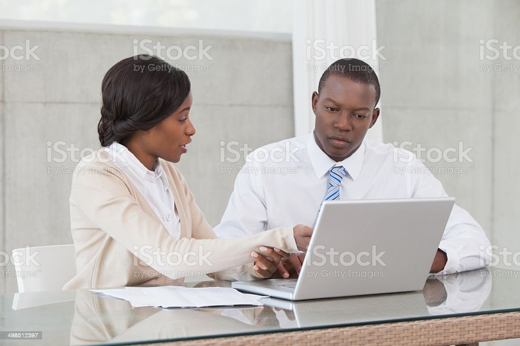 Business partners working on laptop together royalty-free stock photo