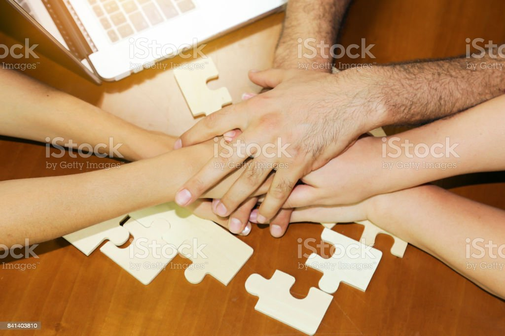 Business partnership or teamwork concept with a business people presenting a matching puzzle piece as they cooperate on finding an answer and solution, close up of their hands. . stock photo