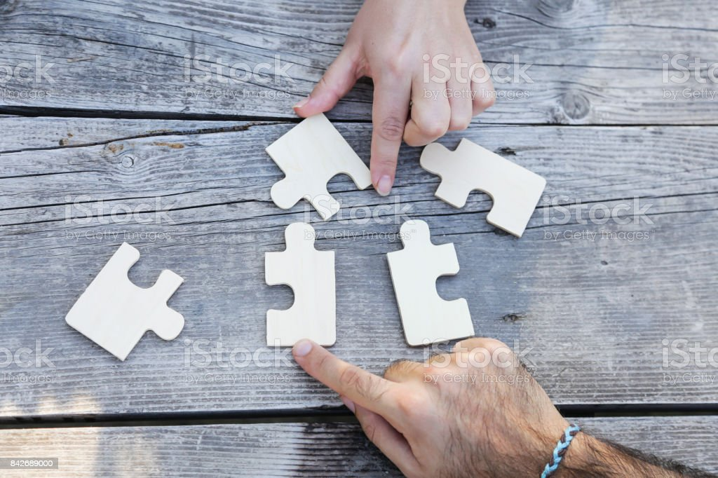 Business partnership or teamwork concept with a business people presenting a matching puzzle piece as they cooperate on finding an answer and solution, close up of their hands. stock photo