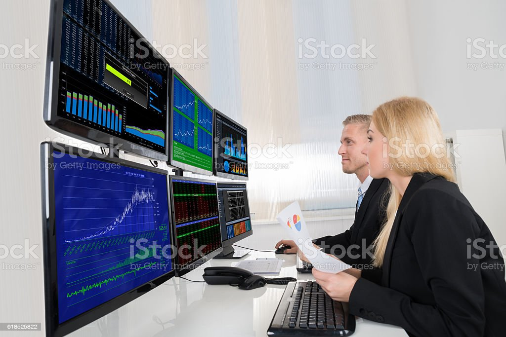 Business People Analyzing Data Displayed On Computer Screens stock photo