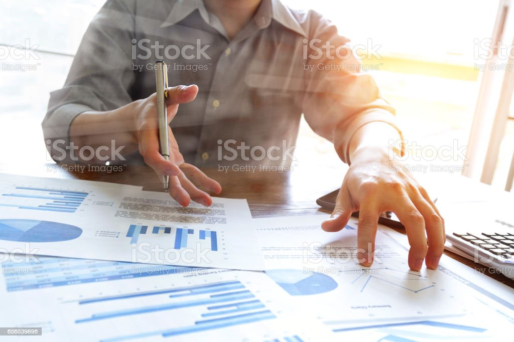 business people analyzing graph and chart document on office desk stock photo