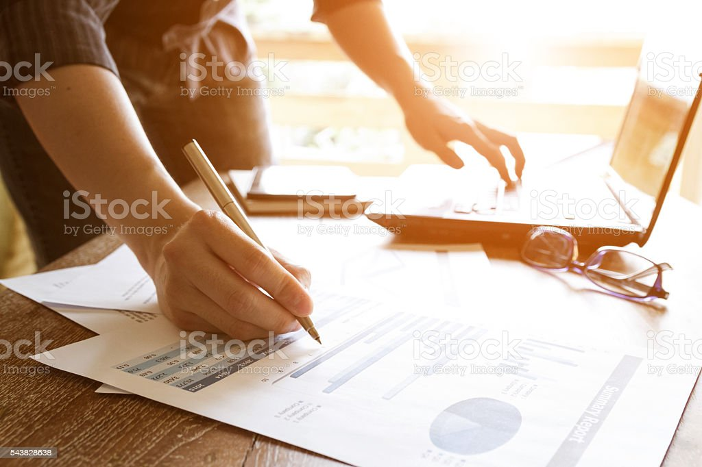 business people analyzing graph and chart document stock photo