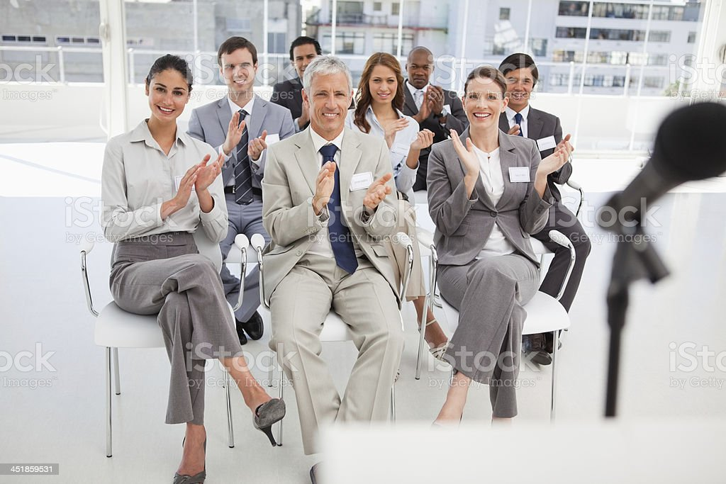 Business people applauding at meeting stock photo