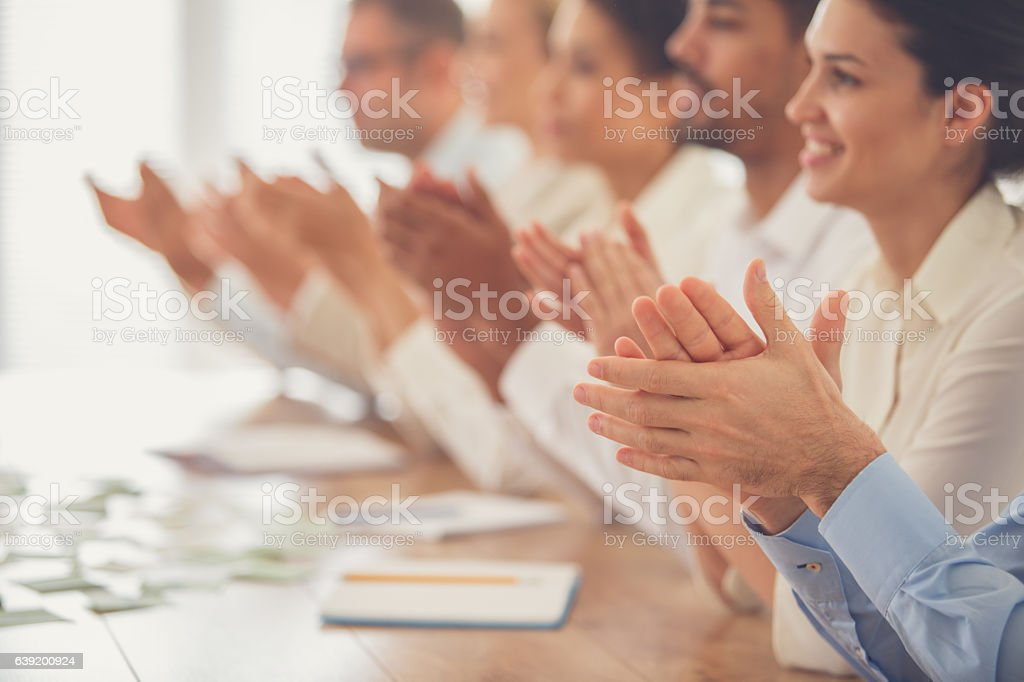 Business people applauding in meeting stock photo