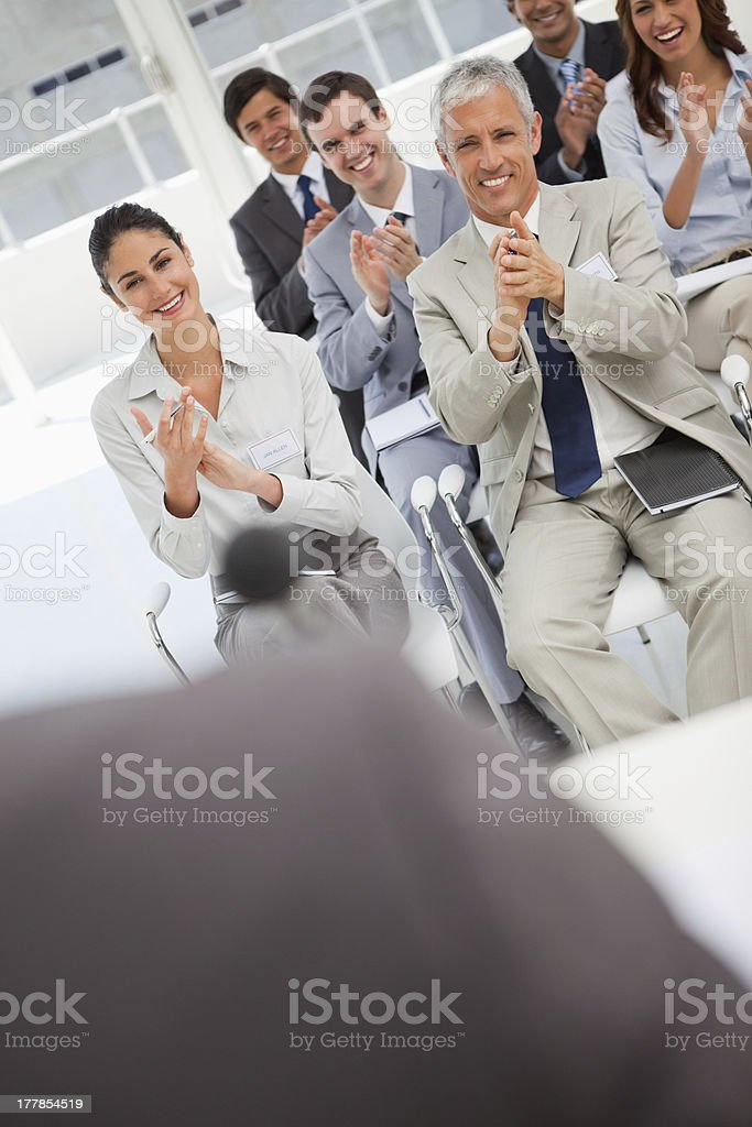 Business people applauding speaker at meeting royalty-free stock photo