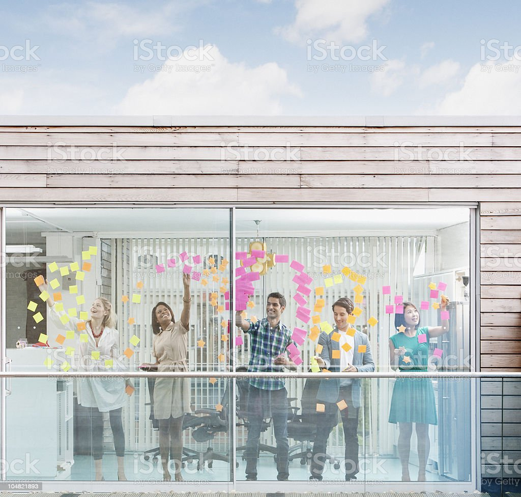 Business people applying adhesive notes to window stock photo