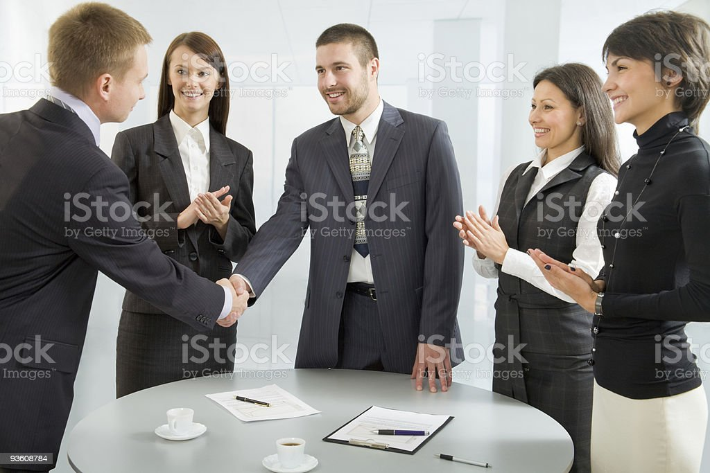 Business people around a table shaking hands stock photo