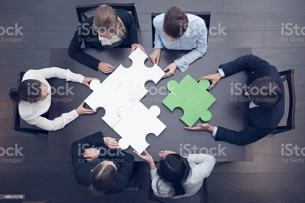 Group of business people assembling jigsaw puzzle, team support and...
