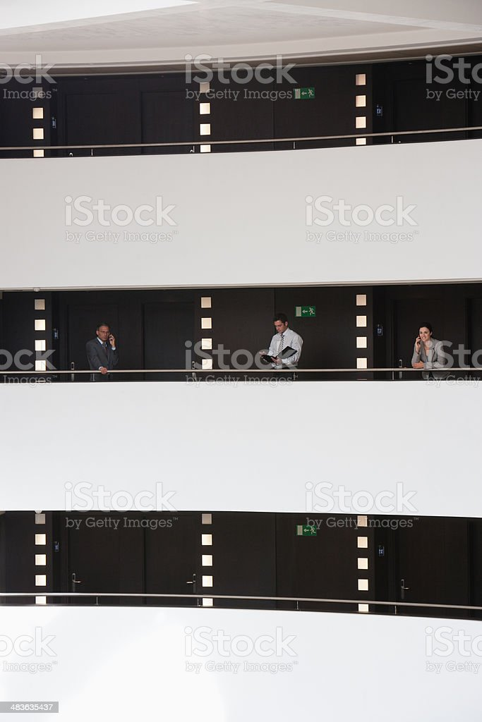 Business people at balcony in atrium stock photo