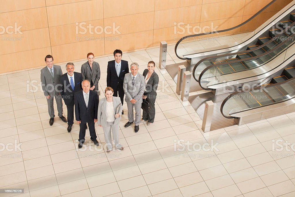 Business people at bottom of escalator royalty-free stock photo