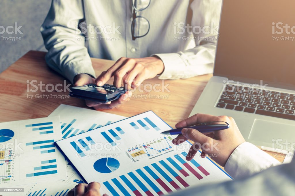 Business people calculate with paper chart analyze on desk and laptop for searching data result. stock photo
