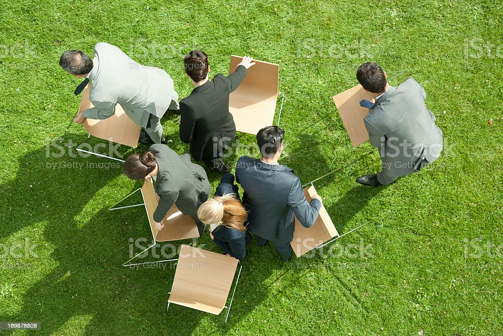 Business people carrying chairs outdoors royalty-free stock photo