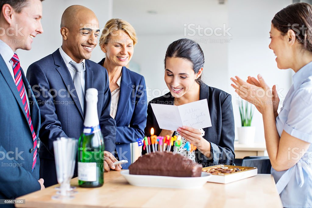 Business people celebrating colleague's birthday in office stock photo