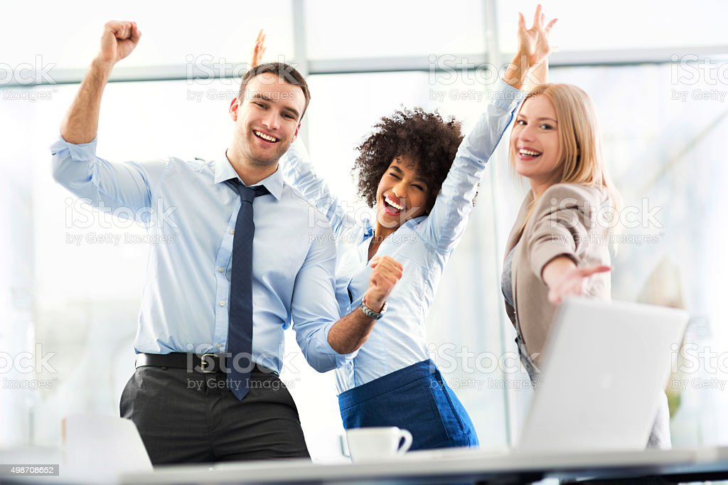 Business people cheering with arms raised stock photo