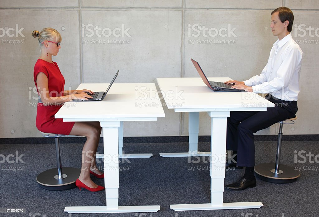 Business people co workers in correct sitting posture at desks stock photo