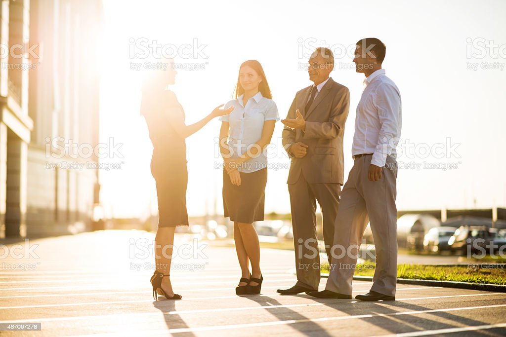 Business people communicating outdoors at sunset. stock photo