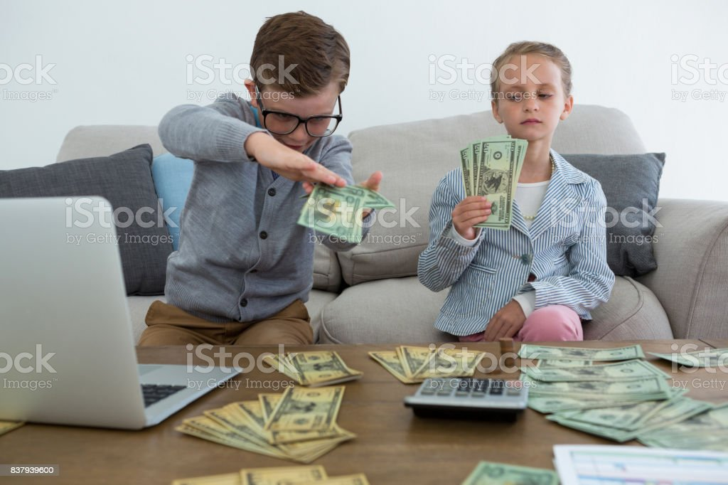 Business people counting currency while sitting on sofa stock photo