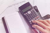 Business people counting on calculator, notebook, holding pen in hand