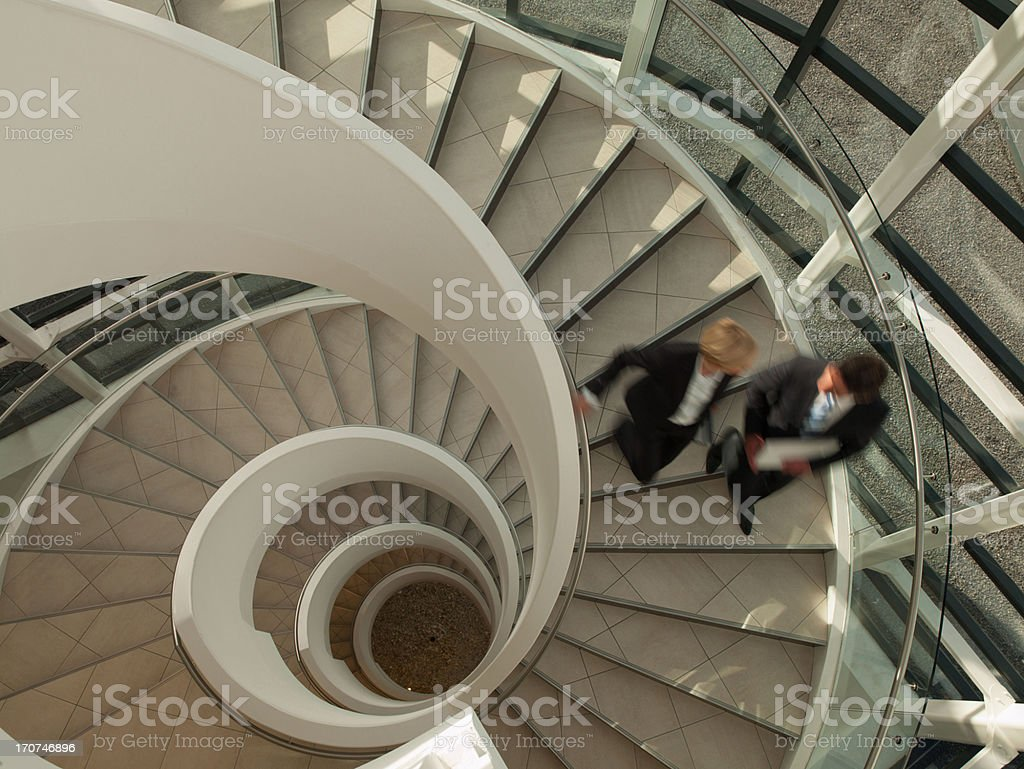 Business people descending circular staircase stock photo