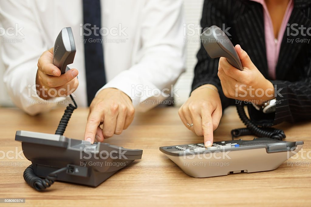 business people dialing on landline telephone to contact clients stock photo