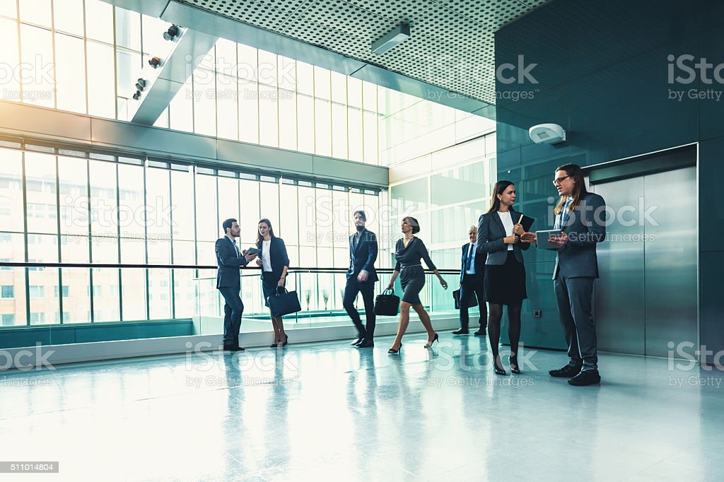 Business people discussing at the lobby stock photo