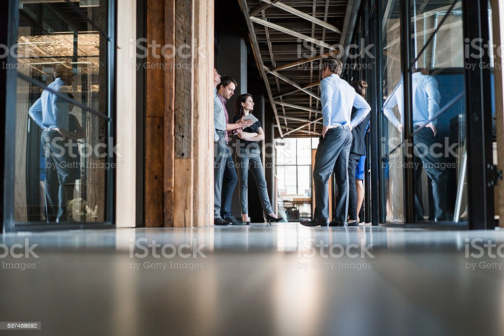 Business people discussing in office corridor stock photo