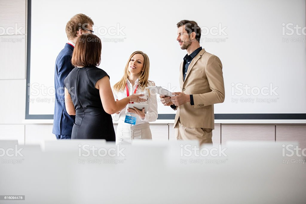 Business people discussing in seminar hall stock photo