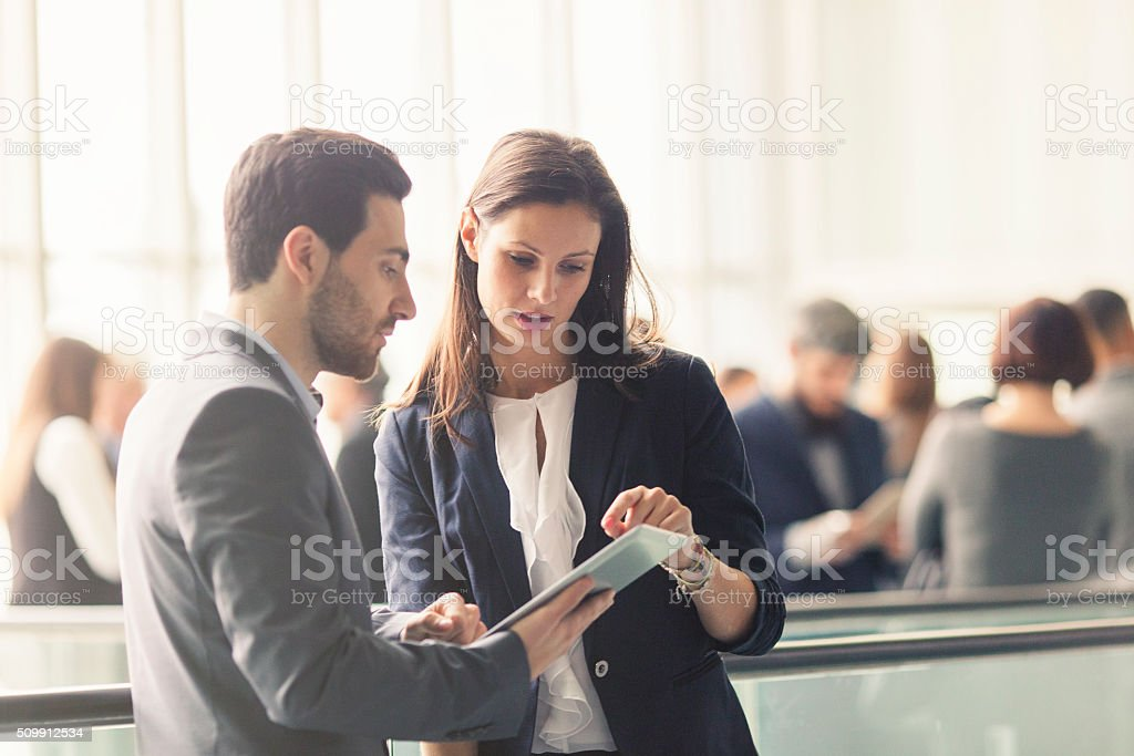 Business people discussing in the lobby stock photo