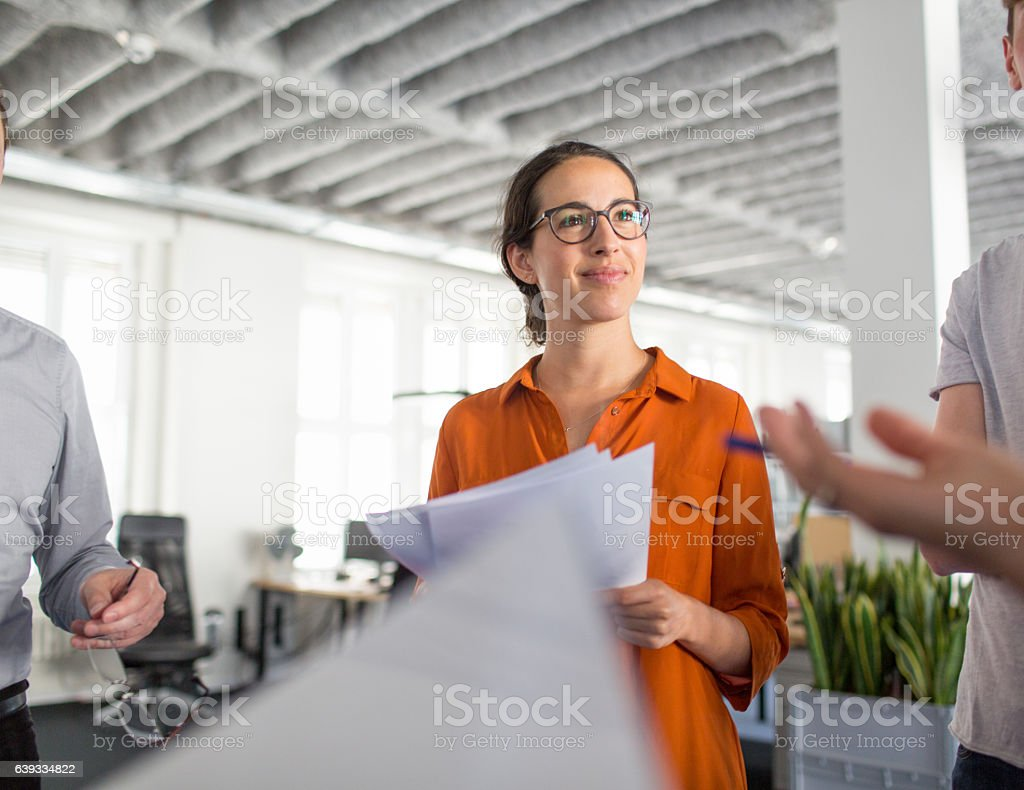Business people discussing on documents at startup office stock photo