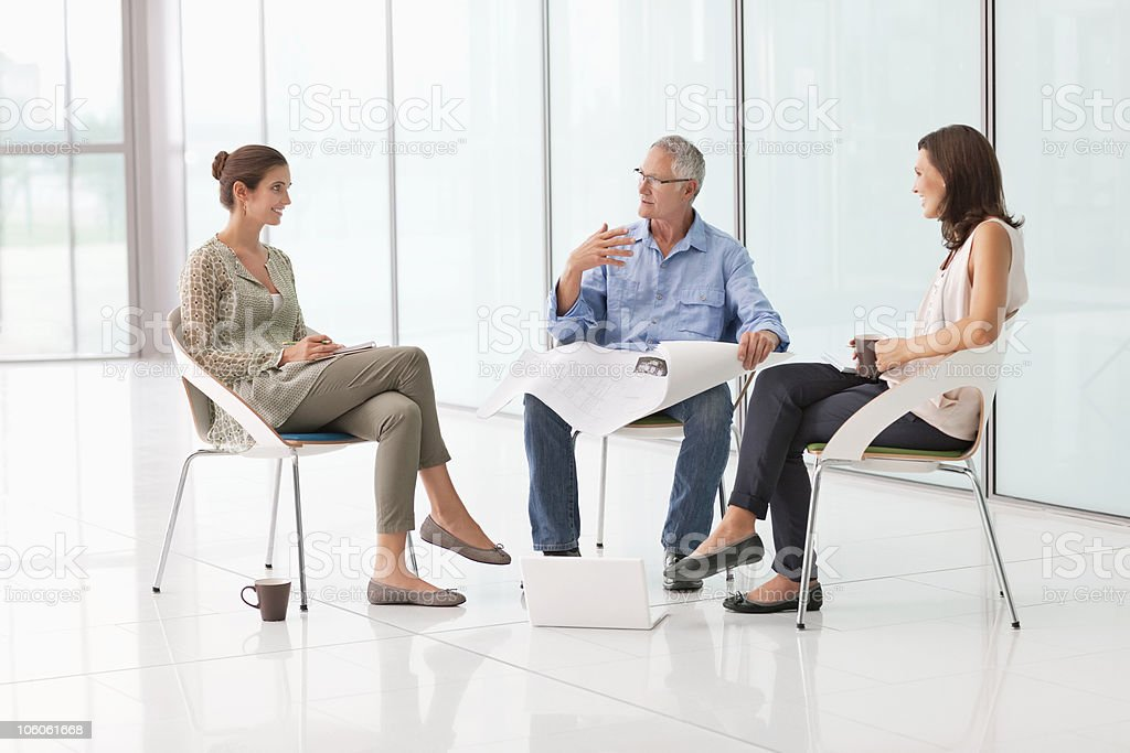 Business people discussing over a blueprint royalty-free stock photo