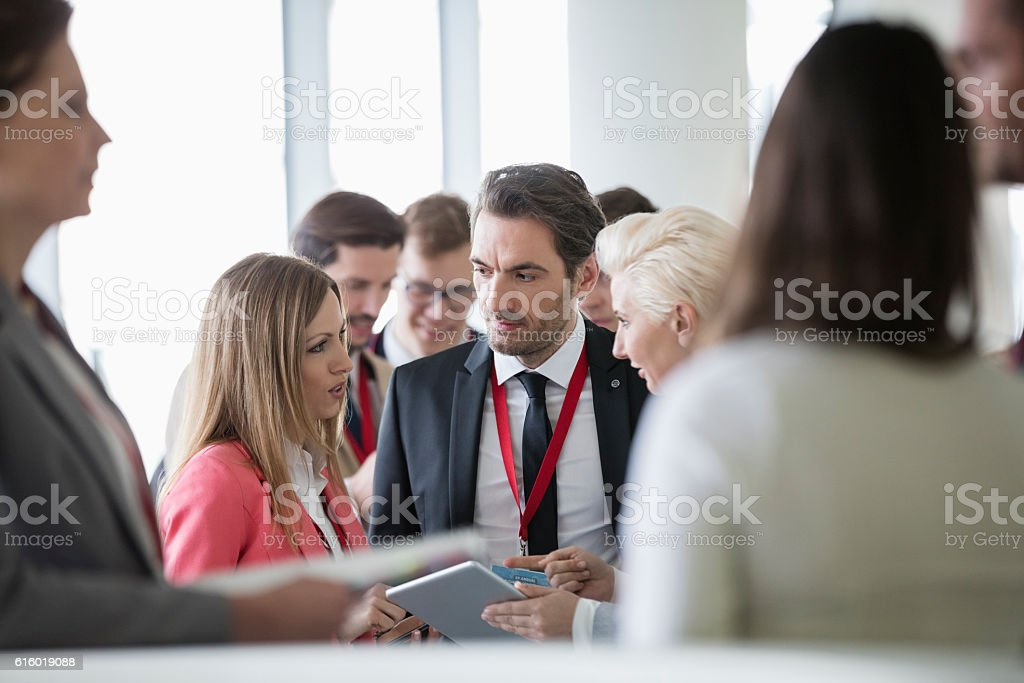 Business people discussing over digital tablet in convention center stock photo