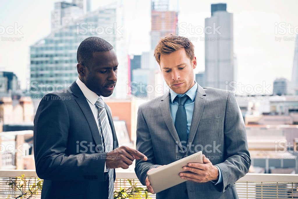 Business people discussing project on digital tablet stock photo