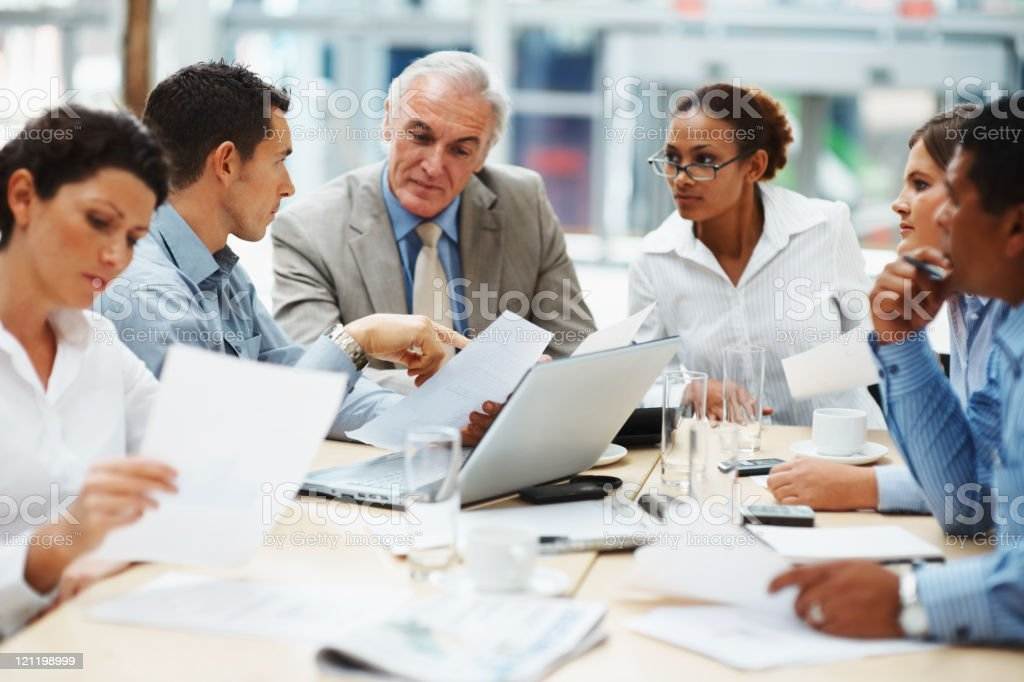 Business people discussing work on laptop at a meeting stock photo