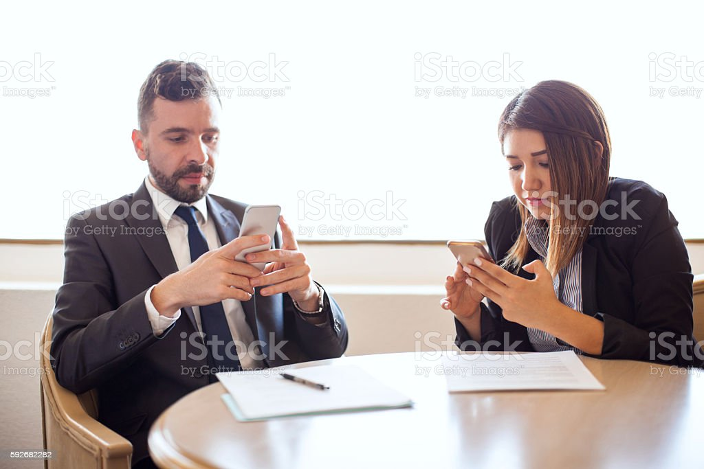 Business people distracted with their smartphones stock photo