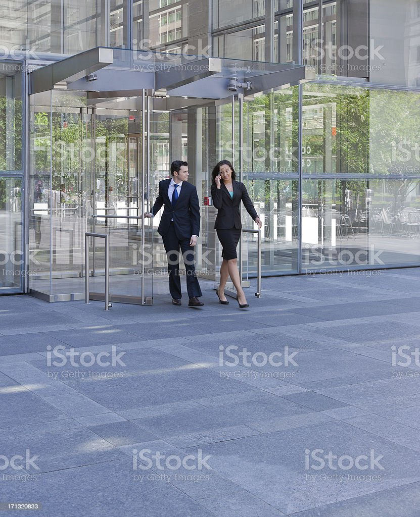 Business people exiting through glass doors stock photo