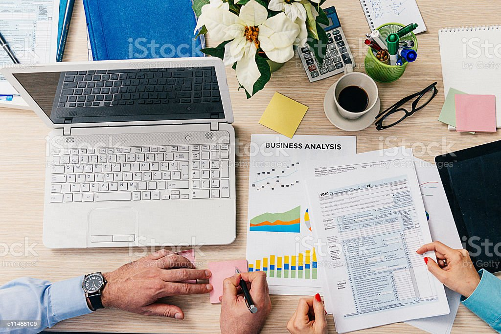 Business people filling out IRS tax form 1040 in office stock photo