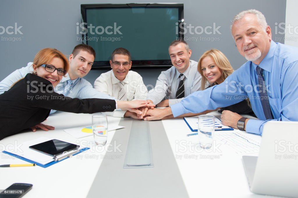 Business people gathering hands in unity celebrating team spirit. stock photo