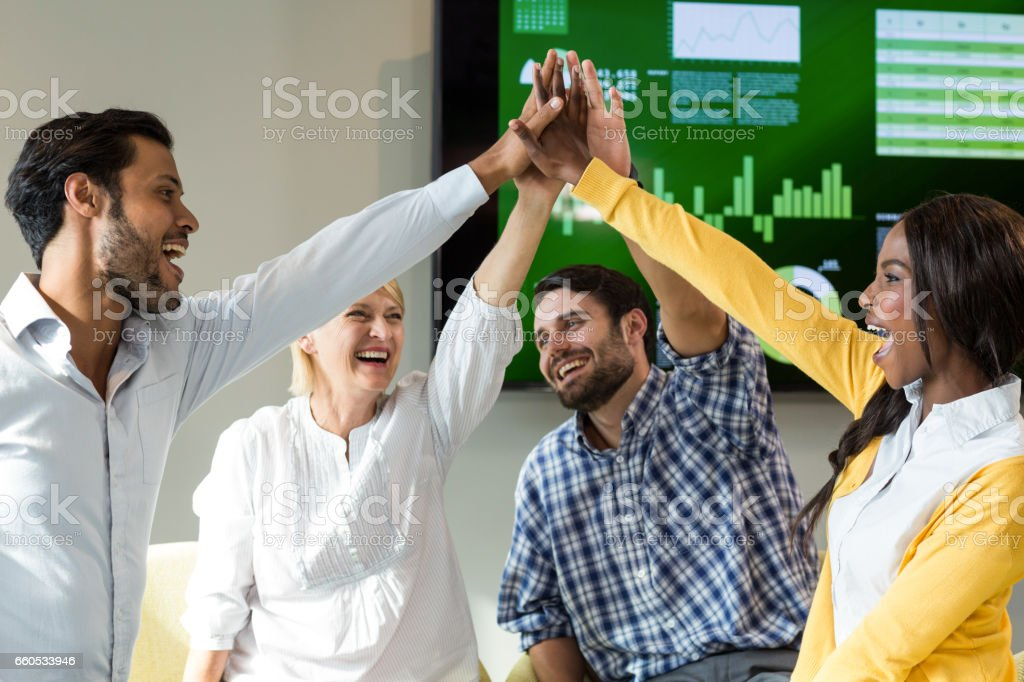 Business people giving high five at desk stock photo